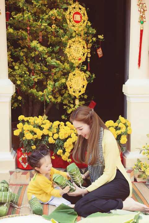 Riêng bé Cadie Mộc Trà, với trang phục tông   xuyệt tông cùng mẹ, khoe vẻ đáng yêu, nụ cười tươi tắn như thiên thần.   Cô bé còn cùng mẹ thực hiện những động tác gói bánh Tét hay cảnh bé trao   cho mẹ quả dưa đầy giữa không gian ngập sắc vàng của hoa mai phương   Nam.