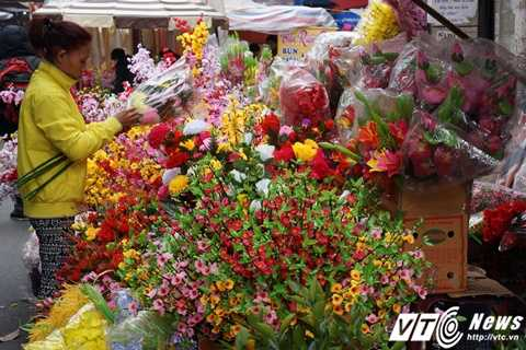 Rất nhiều cành nụ, hoa lá giả có màu sắc rực rỡ được trưng bày tại khu vực chợ hoa Tết phố cổ năm nay.