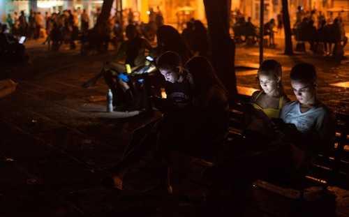 Thanh niên Cuba vào Internet bằng thiết bị di động, tại một điểm phát wi-fi công cộng