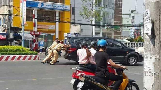 Cảnh sát giao thông đẩy ô tô chết máy giúp dân. Ảnh: Facebook.