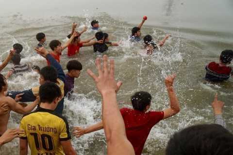 Một người sau khi giành được quả phết phải nhảy xuống sông bơi qua bờ bên kia để có thể thoát được đám đông đang vây đuổi. Ảnh: Hiếu Trần.