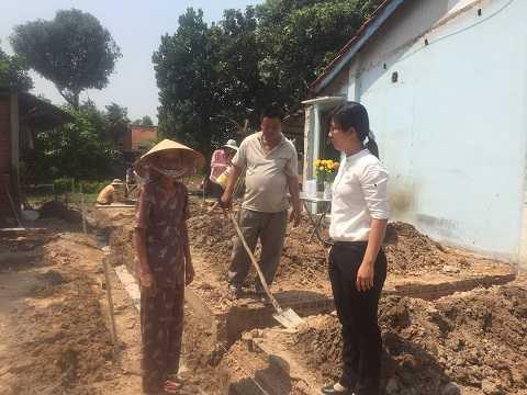 Mẹ Lê Thị Kiều Oanh (đội nón) vui mừng khi tiếp chuyện với Chủ tịch UBND xã Tân Thông Hội (nữ áo trắng). Ảnh: Phan Cường