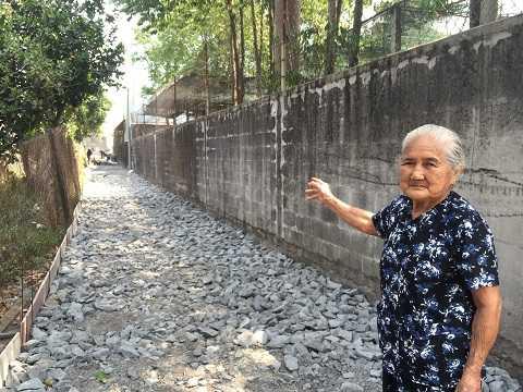Mẹ Nguyễn Thị Em không nén được niềm vui khi con đường vào nhà mình được trải bêtông. Ảnh: Phan Cường