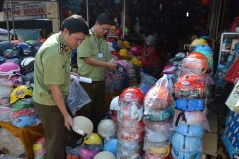 Phó Chánh Thanh tra Sở bị dân vây đòi tiền Ông Trần Nguyễn Đức (phía ngoài) trong lần kiểm tra mũ bảo hiểm giả. Ảnh: QA