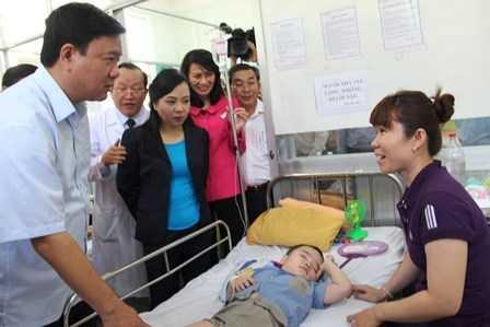 Bí thư Thành ủy TP HCM Đinh La Thăng cùng Bộ trưởng Bộ Y tế Nguyễn Thị Kim Tiến thăm hỏi người nhà của một bệnh nhi đang điều trị ở bệnh viện Bình Tân. Ảnh: Phan Tư