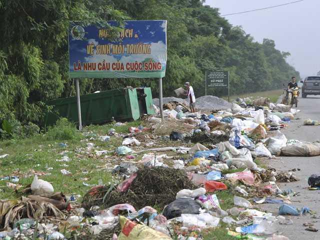 """Biển báo giữ vệ sinh môi trường sạch đẹp """"ngập ngụa"""" trong đống rác (Ảnh chụp ở khu vực Sơn Tây tháng 10/2015)."""