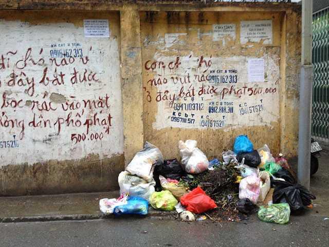 Những dòng chữ răn đe cùng hình phạt 500.000 đồng cũng không làm người dân thôi đổ rác. (Ảnh chụp tại phố Yên Hòa, Cầu Giấy tháng 1/2016)