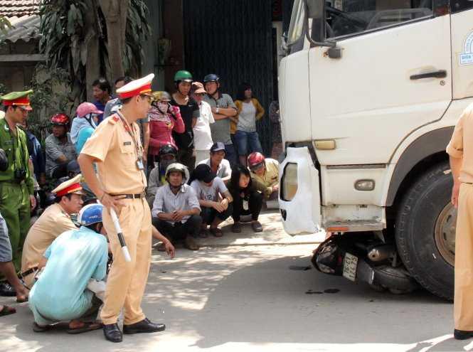 Cơ quan công an khám nghiệm hiện trường vụ tai nạn giao thông giữa xe tải và xe máy - Ảnh: Trần Mai