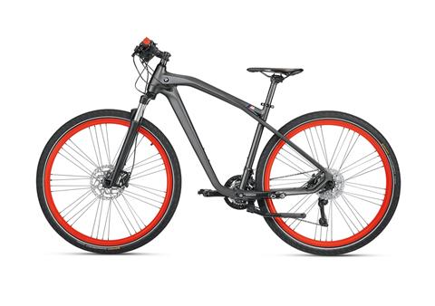 Xe Trail Bike Cruise M có tay lái đen mờ, điểm nhấn màu đỏ cam tại bánh xe và các chi tiết bằng sợi cacbon