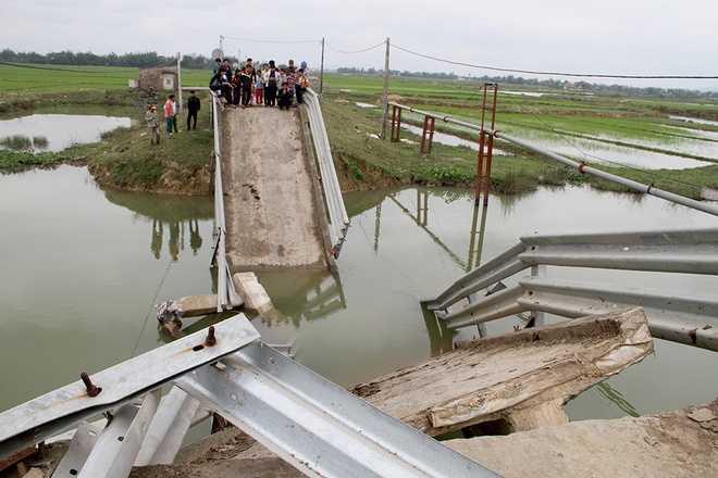 Những mảng bê tông đổ sập xuống lòng sông đồng thời nhấn chiếc sà lan xuống nước. 3 người trên sà lan rơi xuống sông, may mắn thoát chết.