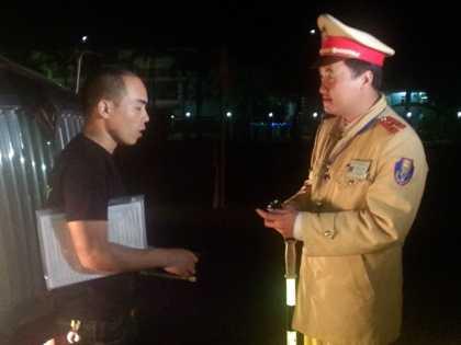 Đại úy Dương Công Huy nhắc nhở tài xế xe BKS 15C-157.01 không được dừng đỗ ở đoạn đường nguy hiểm. Ảnh Đ.A