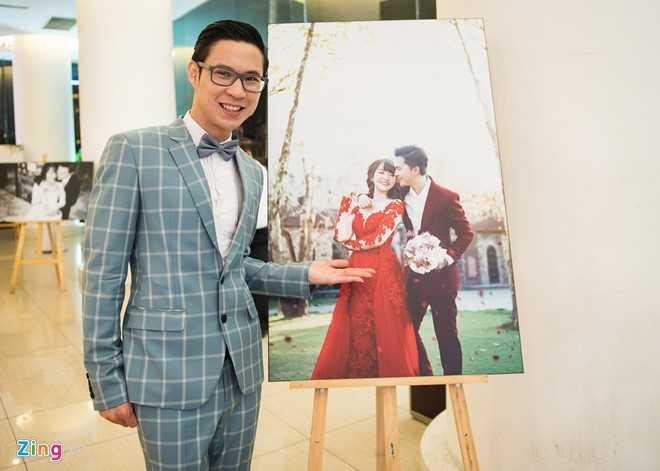 MC Anh Quân tạo dáng bên tấm ảnh cưới lãng mạn của đôi vợ chồng trẻ.