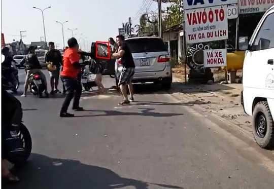 Bị tấn công hội đồng, tài xế ô tô buộc phải dùng một vật giống dao (vùng khoanh đỏ) chống trả. (Ảnh: Cắt từ clip)