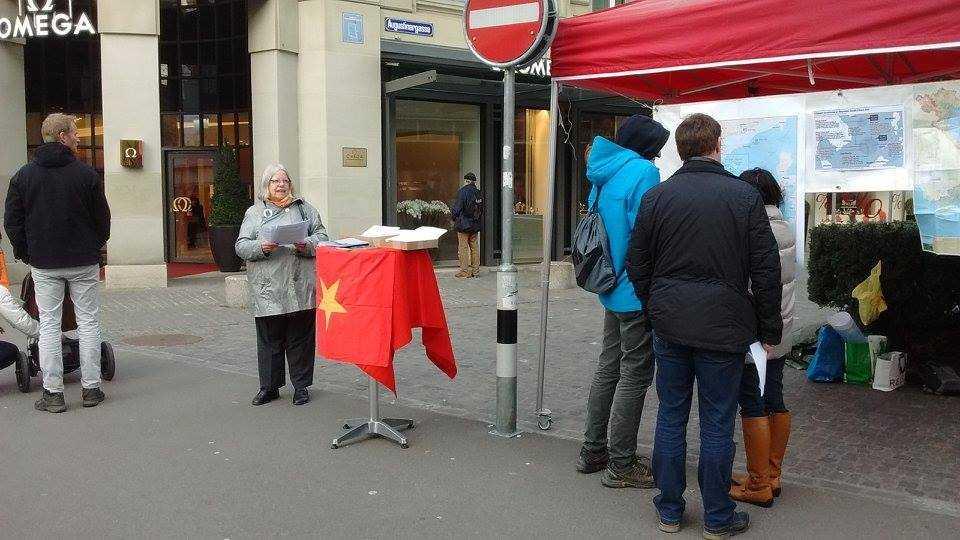 Bà Anjuska Weil, chủ tịch Hội hữu nghị Thụy Sĩ – Việt Nam bên quầy thông tin với xấp tờ rơi thông tin về những hành động vi phạm trắng trợn luật pháp quốc tế gần đây của Trung Quốc trên biển Đông. Hơn 100 tờ thông tin được phân phát cho mọi người trên đường phố Zurich