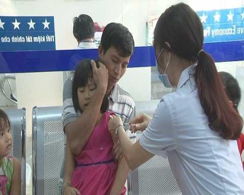 Một người bố đưa con đến Trung tâm Y tế để tiêm vacxin Ảnh:Thanh Hải