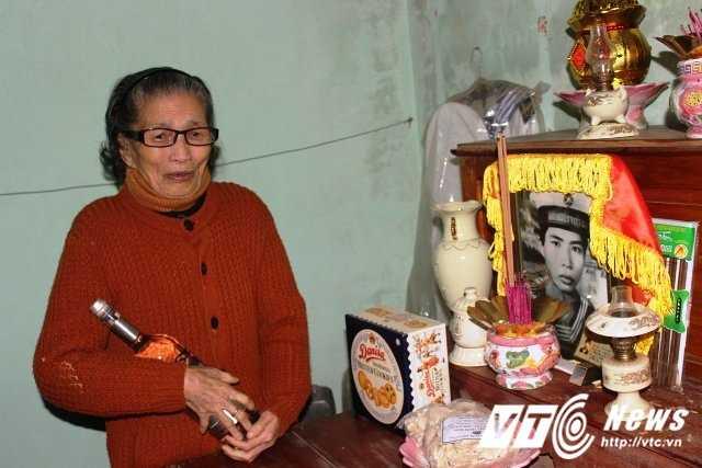 Mẹ Giỏ ôm chai nước biển trước bàn thờ liệt sĩ Tống Sĩ Bái