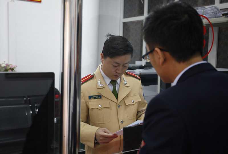 Anh Phạm Duy Dương (áo đen) đến cơ quan công an chứng minh chiếc xe vi phạm theo thông báo không phải là xe nhà mình.