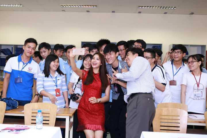 """Bộ đầm đỏ ren tưởng chừng như đơn giản nhưng lại giúp Phạm Hương khoe vóc dáng nuột nà với vòng eo đáng ngưỡng mộ. Hơn nữa, sắc đỏ khiến cô trở nên nổi bật hơn khi ở trong """"vòng vây"""" của các bạn sinh viên"""