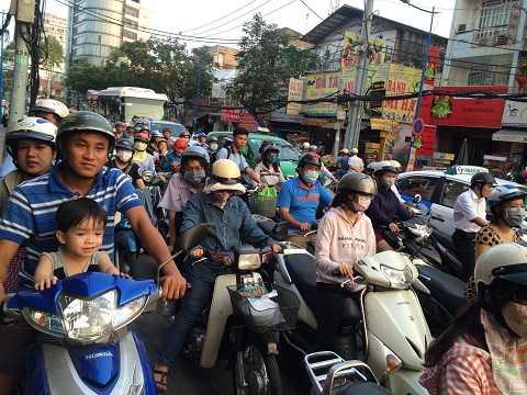Các em nhỏ, học sinh cũng như phụ huynh nhẫn nhịn đứng chờ đợi trong dòng người xe chen chúc. Ảnh: Thanh Qúy