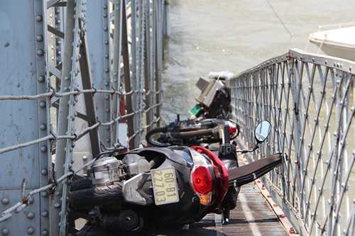 Xe máy của những người bị rơi xuống sông còn mắc lại trên cầu (Ảnh: Hoàng  Trường/VNE)