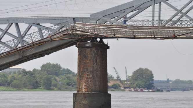 Chiếc sà lan va vào móng cầu khiến 2 nhịp cầu bị gãy. Ít nhất 3 người đang chạy xe máy trên cầu rớt xuống sông, tuy nhiên tất cả đã được cứu kịp thời. (Ảnh: Bạn đọc Nguyen Trong Hieu/TTO)