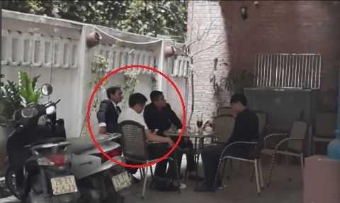 3 người đàn ông canh giữ không cho phóng viên Quang Hải rời khỏi quán cà phê.