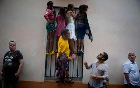Người dân Cuba leo lên hành lang, cửa sổ để nhìn đoàn xe của Tổng thống Mỹ đi qua