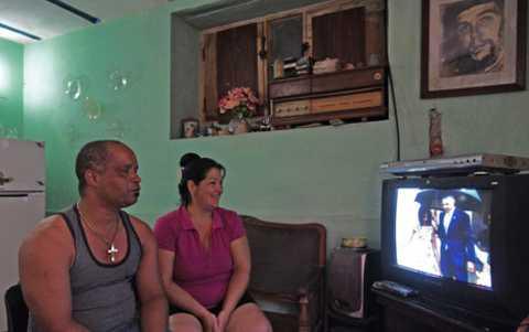 Hai vợ chồng sinh sống ở La Habana theo dõi ti vi đang chiếu bản tin nói về chuyến thăm lịch sử Cuba của Tổng thống Obama.