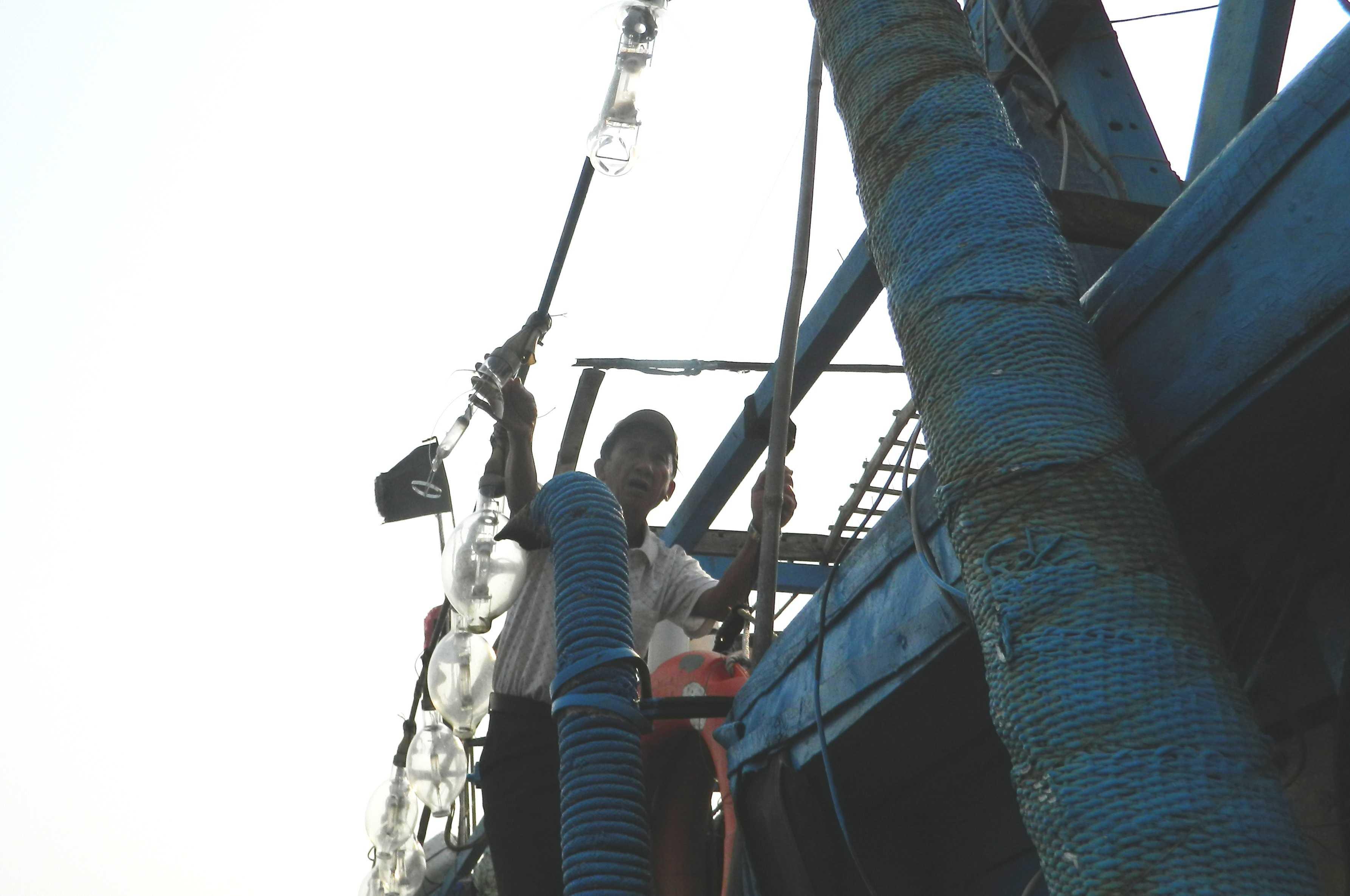 Ngư dân sinh đã thay lại bóng đèn chong cá bị Trung Quốc bắn bể.