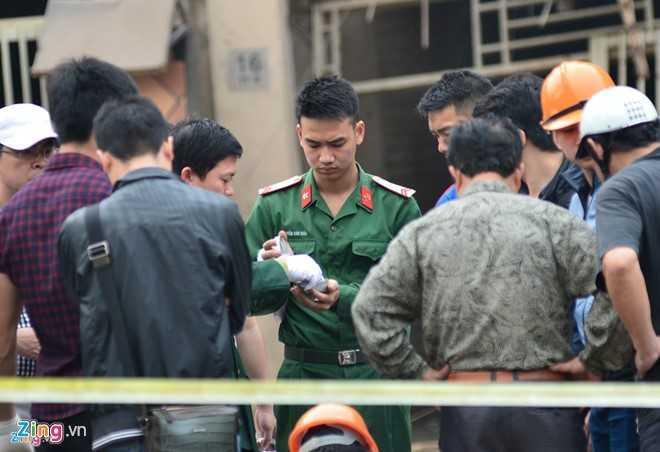 Lực lượng chức năng thu giữ mảnh vỡ của vật nổ. Ảnh: Việt Hùng.