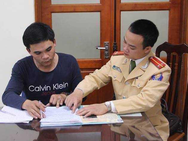 Tài xế Diệp (trái) ký vào biên bản xử phạt