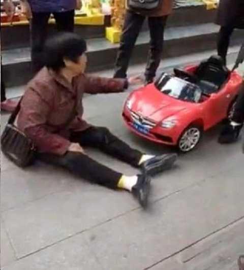 Người phụ nữ ngồi ăn vạ trên vỉa hè để đòi bồi thường. Ảnh Shanghaiist