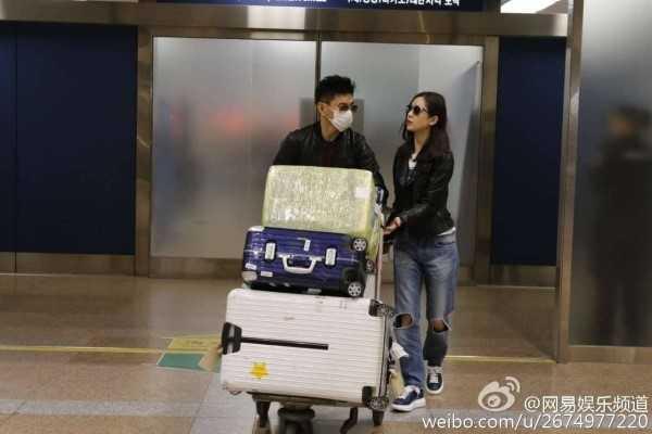 Ngô Kỳ Long chủ động đẩy vali hành lý thay cho vợ. Ảnh: Sina.