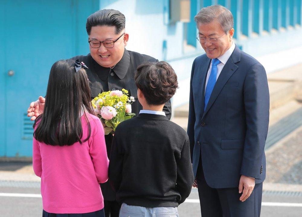 Hai em nhỏ ở làng biên giới tặng hoa và chụp ảnh cùng hai nhà lãnh đạo.