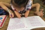 Ảnh: Giờ học của cô bé 8 tuổi cụt tay, dùng chân nắn nót viết chữ đẹp