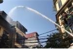 Ảnh: Cảnh sát phun nước dập tắt đám cháy trên phố trung tâm Hà Nội