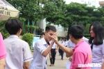 Thầy cô mặc đồng phục màu hồng đứng trước cổng, chào đón học sinh hoàn thành bài thi