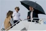 Tổng thống Trump che ô một mình, để vợ con đội mưa lên máy bay