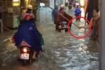 Clip: Người phụ nữ đứng trên phố ngập, lăm le cầm gậy vụt người đi đường
