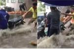Clip: Nước chảy xiết như lũ, dân vật lộn giữ xe máy trong mưa lớn