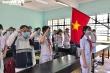 Học sinh chào cờ trong lớp học ngày trở lại trường